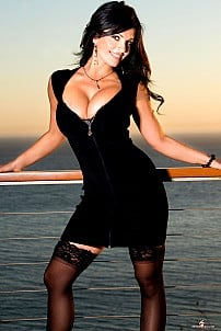 Denise Milani in black lingerie and stockings posing outdoor in the evening