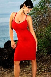 Denise Milani posing outdoor in red dress