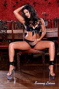 Sunny Leone in black lingerie on chair