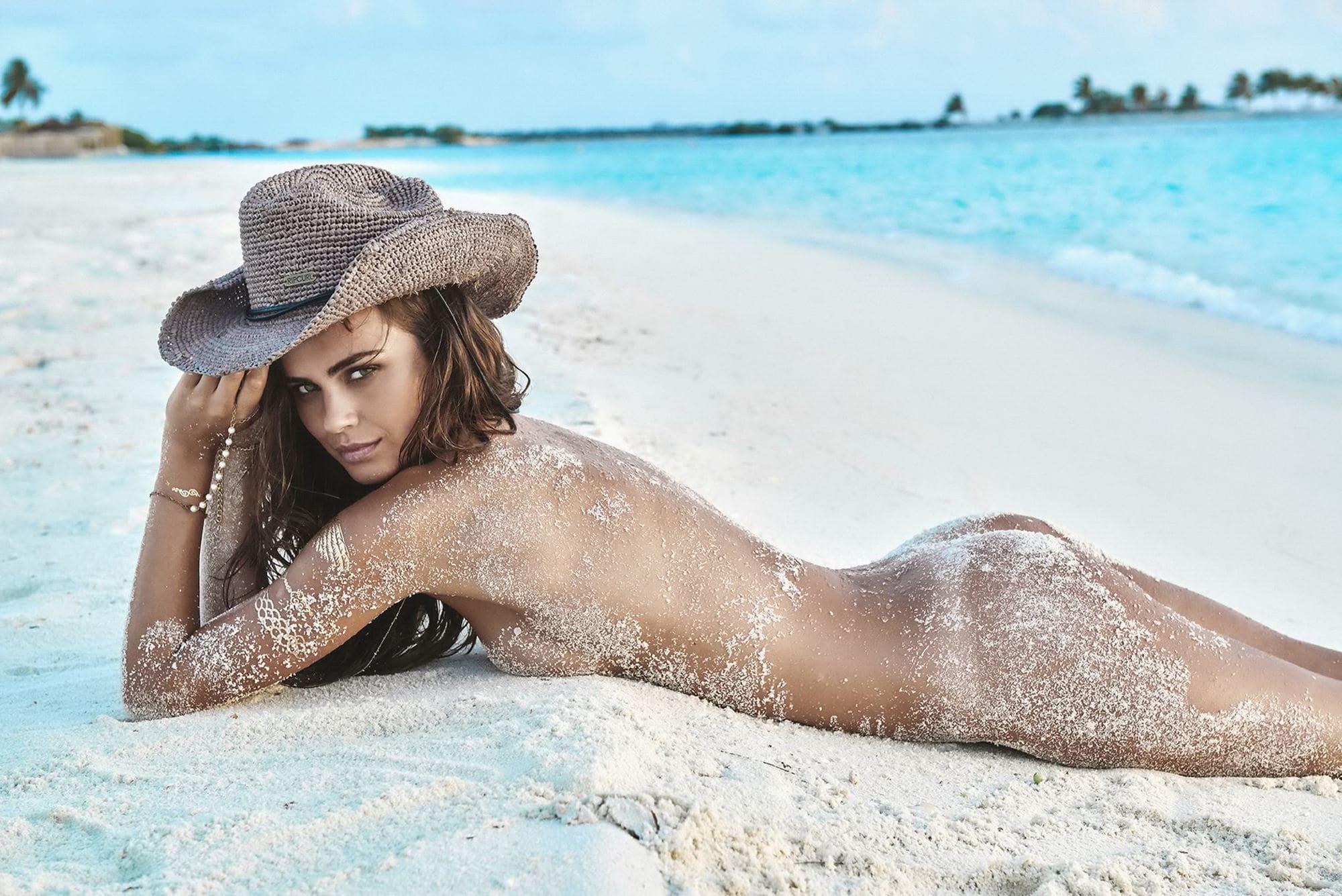 Обнаженная модель красиво позирует на песочке  163015